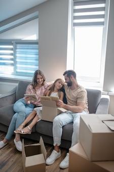 Familia joven sentada en el sofá y mirando fotografías