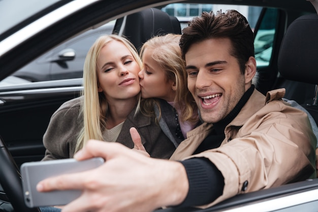 La familia joven sonriente hace selfie por teléfono móvil.