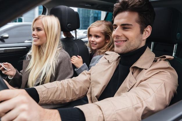 Familia joven sonriente que se sienta en coche