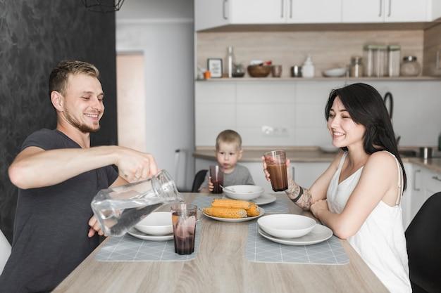 Familia joven con su hijo pequeño desayunando en la cocina