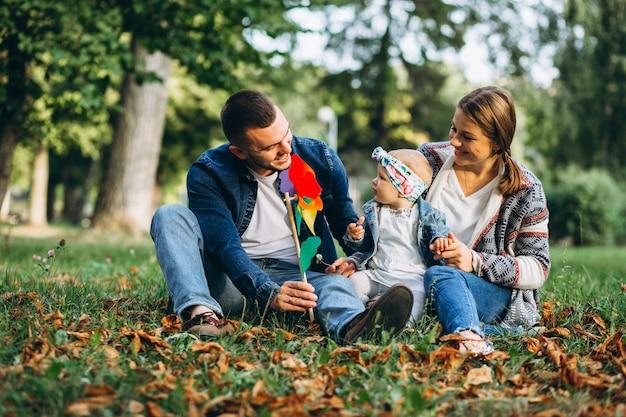 Familia joven con su pequeña hija en el parque otoño