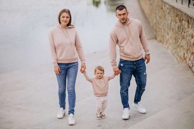 Familia joven con su pequeño hijo bebé en el parque junto al lago