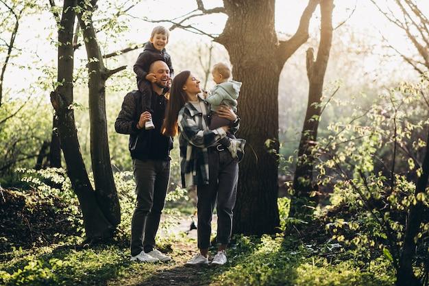Familia joven con sus hijos divirtiéndose en el bosque