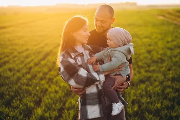 Familia joven con sus hijos divirtiéndose en el campo