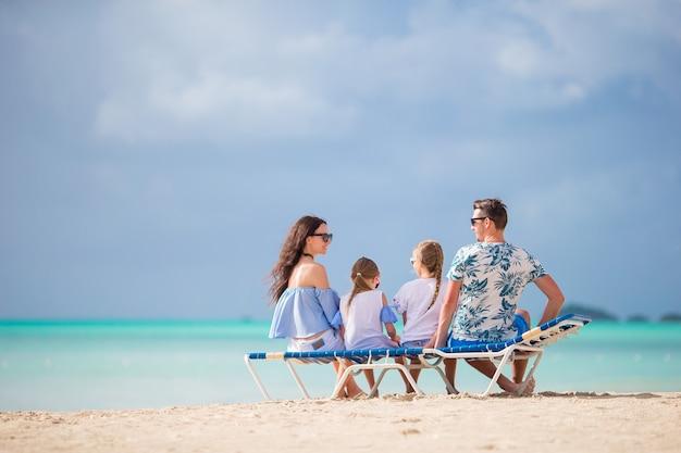 Familia joven de vacaciones. padres e hijos en hamacas disfrutan de la vista al mar.