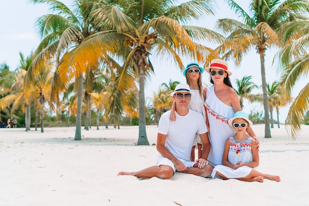 Familia joven en vacaciones en la playa juntos