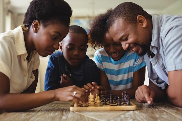 Familia jugando al ajedrez juntos en casa en la sala de estar