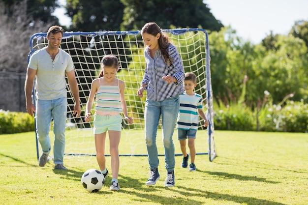 Familia jugando al fútbol juntos en el parque