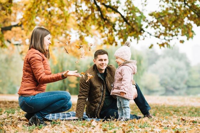 Familia jugando con hojas en el bosque de otoño