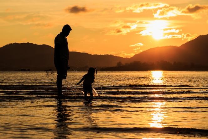 Familia jugando en la playa en el atardecer