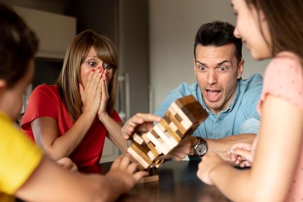 Familia jugando juegos de apilamiento juntos y divirtiéndose