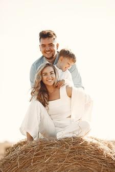 Familia jugando con su hijo en el campo de trigo al atardecer. el concepto de vacaciones de verano. familia pasando tiempo juntos en la naturaleza.