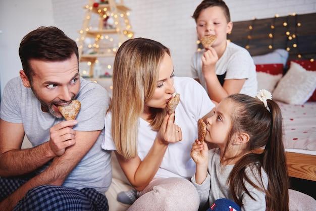 Familia juguetona comiendo galletas de jengibre en la cama