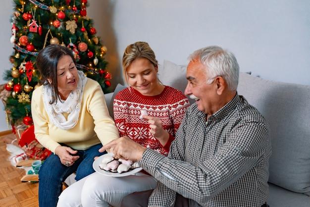 Familia juguetona comiendo galletas de jengibre en casa.