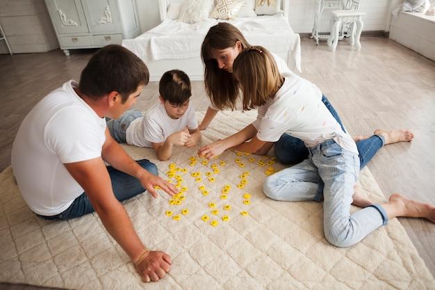 Familia juguetona jugando scrabble juntos en casa