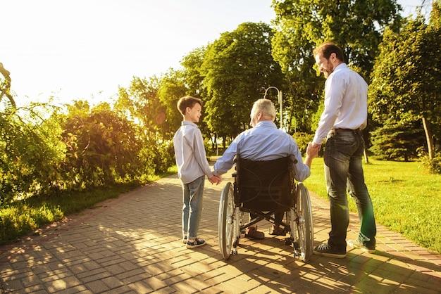 Familia junta. el nieto y el hijo visitan al anciano.