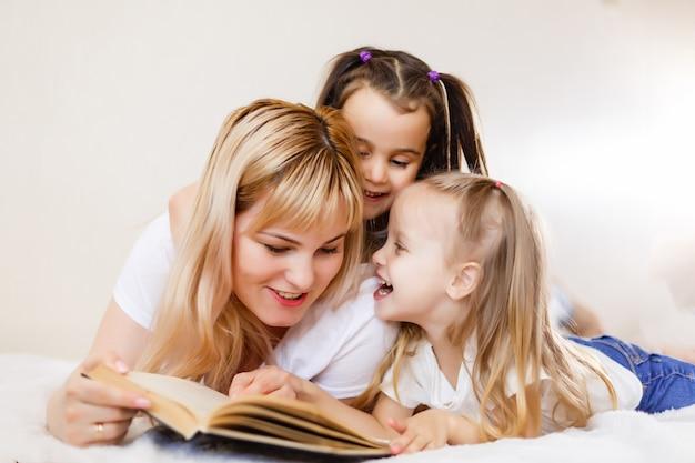 Familia juntos felices madre con dos hijas casa relajante jugando. retrato familiar.