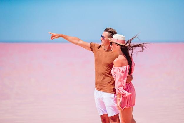 Familia en un lago de sal rosado en un día soleado de verano. explorando la naturaleza, los viajes, las vacaciones familiares.