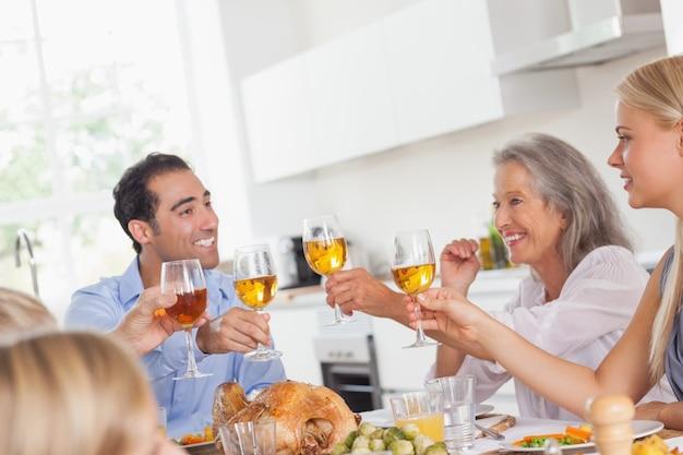 Familia levantando sus copas en la cena de acción de gracias