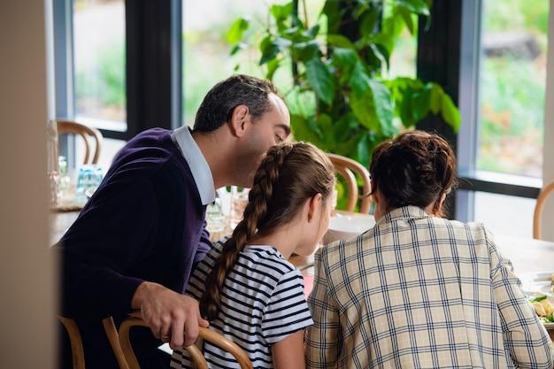 Una familia leyendo algo en la mesa de la cocina, vista desde atrás
