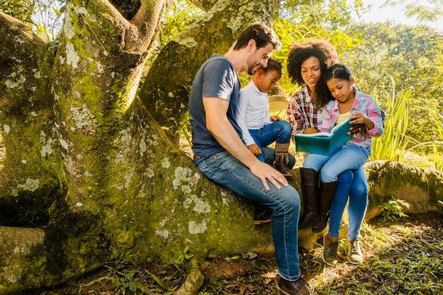 Familia leyendo juntos en un tronco de árbol