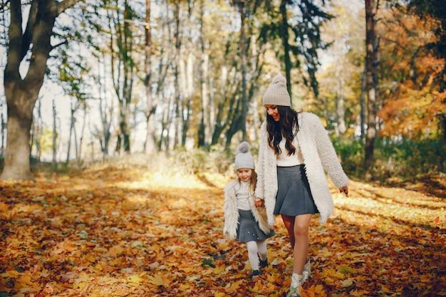 Familia linda y elegante en un parque de otoño
