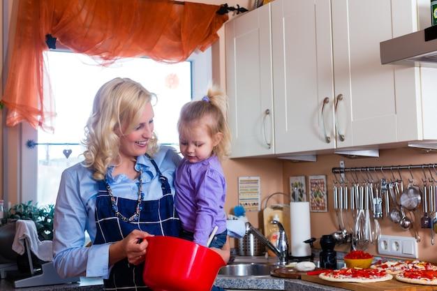Familia - madre e hijo horneando pizza