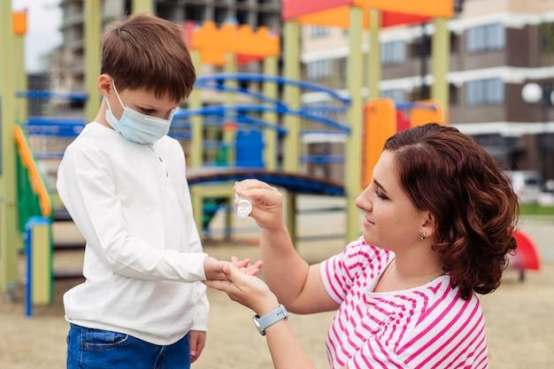 Familia madre e hijo en el patio de recreo. el niño usa una máscara médica protectora durante una epidemia de virus coronario o gripe. equipo de protección personal. madre le da una mano antiséptica a su bebé