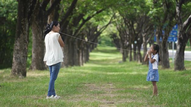 La familia, la madre y la hija asiáticas que hacen las actividades del juego del teléfono de la cuerda ata la cuerda en el parque