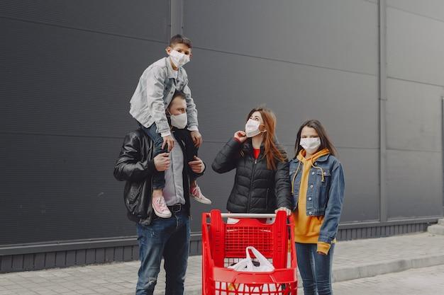 Familia en máscaras protectoras con compras