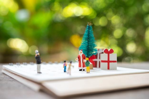 Familia miniatura personas de pie en el árbol de navidad celebran la navidad