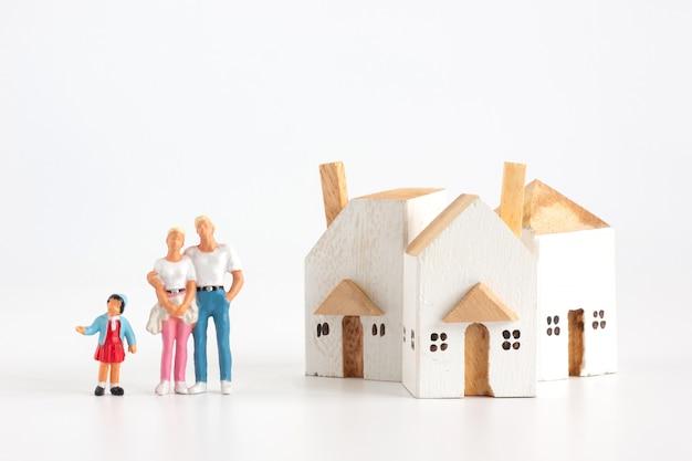 Familia miniatura tiene padre madre e hija con casa sobre fondo blanco.