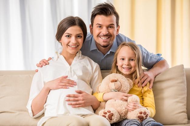 La familia está mirando a la cámara y sonriendo.