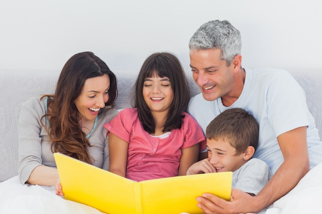 Familia mirando juntos a su álbum de fotos en la cama