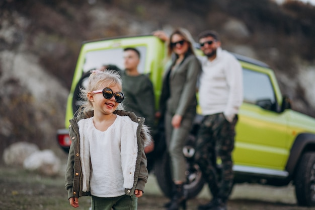 Familia moderna joven que viajaba en coche y se detuvo a caminar en el parque