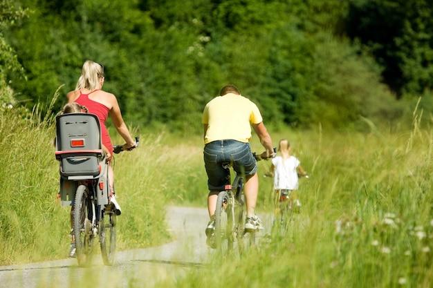 La familia monta la bicicleta