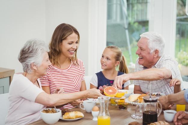 Familia multigeneración comiendo frutas durante el desayuno