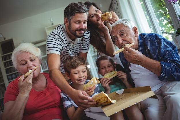 Familia multigeneración comiendo pizza juntos