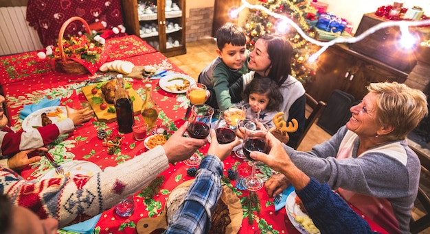 Familia multigeneración feliz divirtiéndose en la cena de navidad