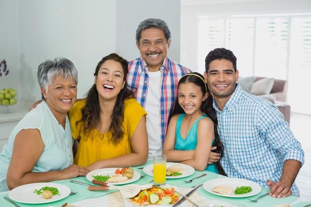 Familia multigeneración feliz que tiene comida en la mesa en casa