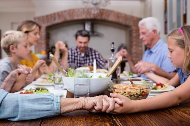 Familia multigeneración orando antes de comer