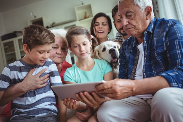 Familia multigeneración con tableta digital en sala de estar