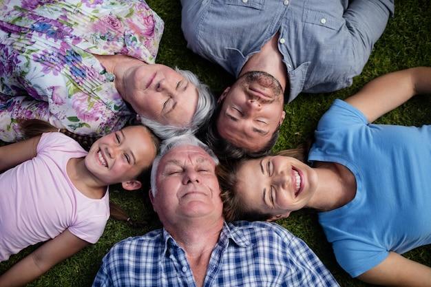 Familia multigeneración tumbados juntos en el jardín