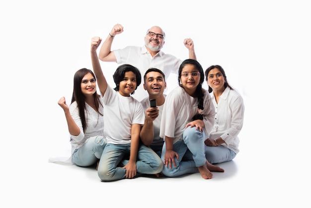 Familia multigeneracional asiática india de seis viendo la televisión juntos en casa y divirtiéndose, sentados en el piso contra el fondo blanco.