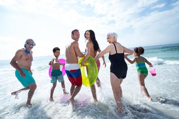 Familia multigeneracional riendo y corriendo en la playa