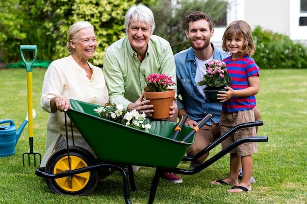 Familia de múltiples generaciones con herramientas de jardinería en el patio