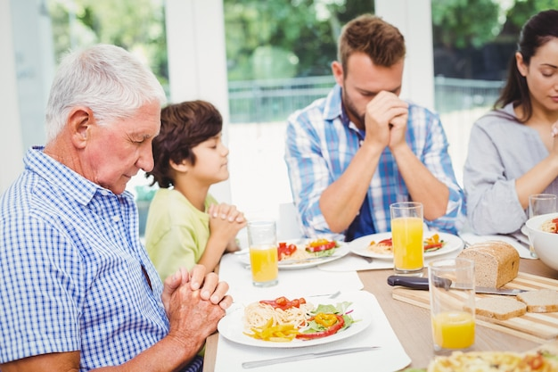 Familia de múltiples generaciones rezando en la mesa del comedor