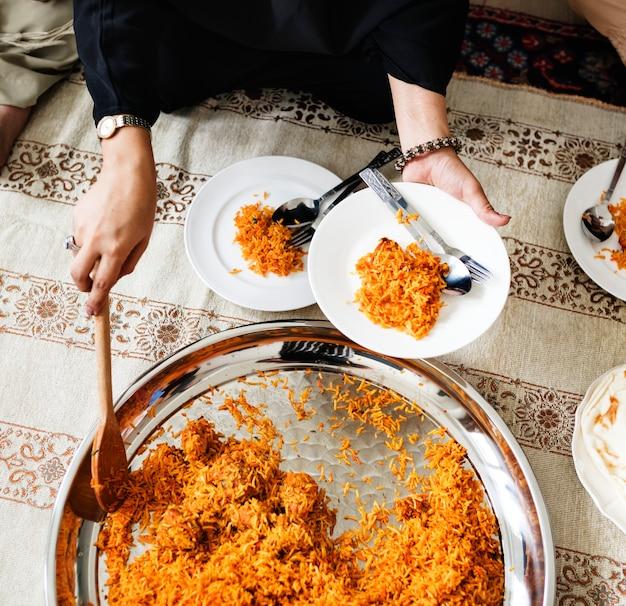 Familia musulmana cenando en el piso