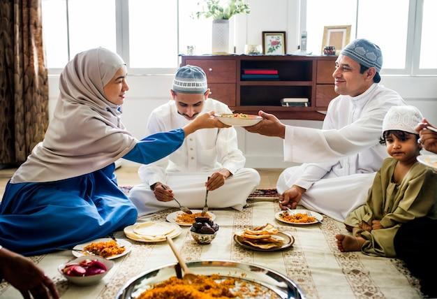 Familia musulmana cenando en el suelo.