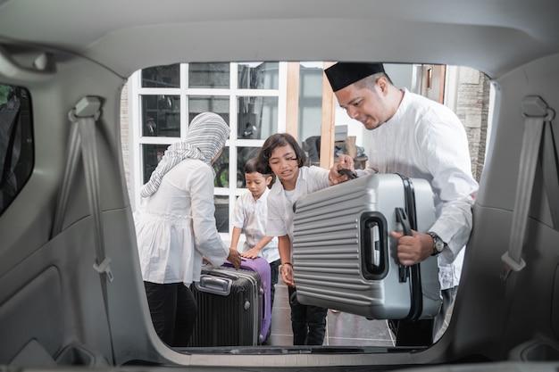 Familia musulmana colocando maletas en el auto